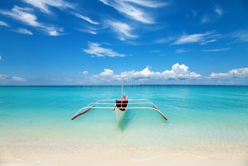 Barco blanco en una playa tropical foto de archivo