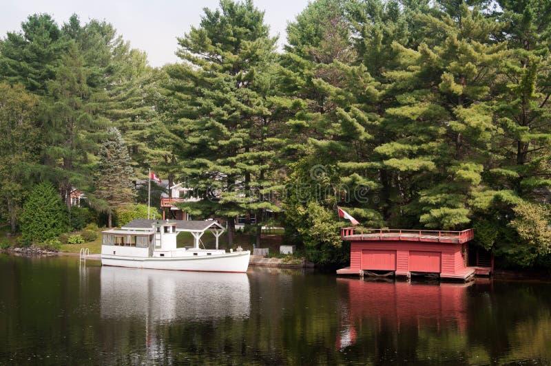 Barco branco e boathouse vermelho imagem de stock