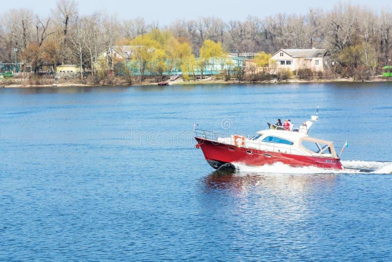 Barco branco vermelho que flutua no rio imagem de stock