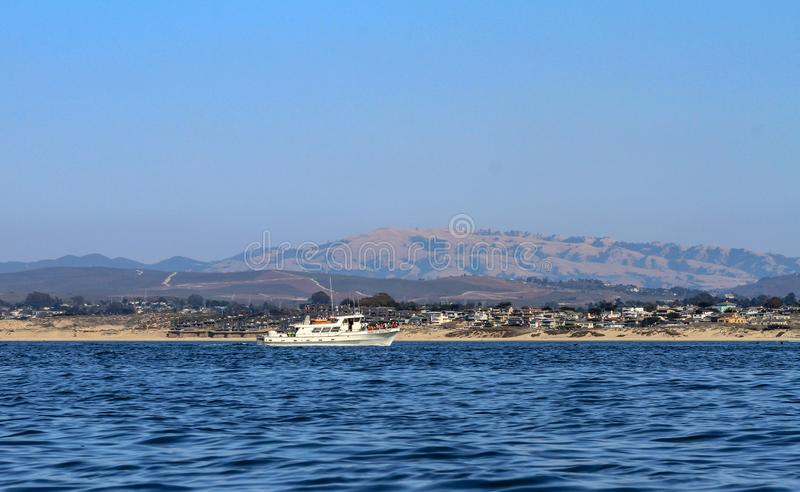 Barco branco visto do mar contra a costa imagem de stock