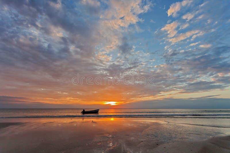 Barco cerca de la playa en la puesta del sol fotos de archivo