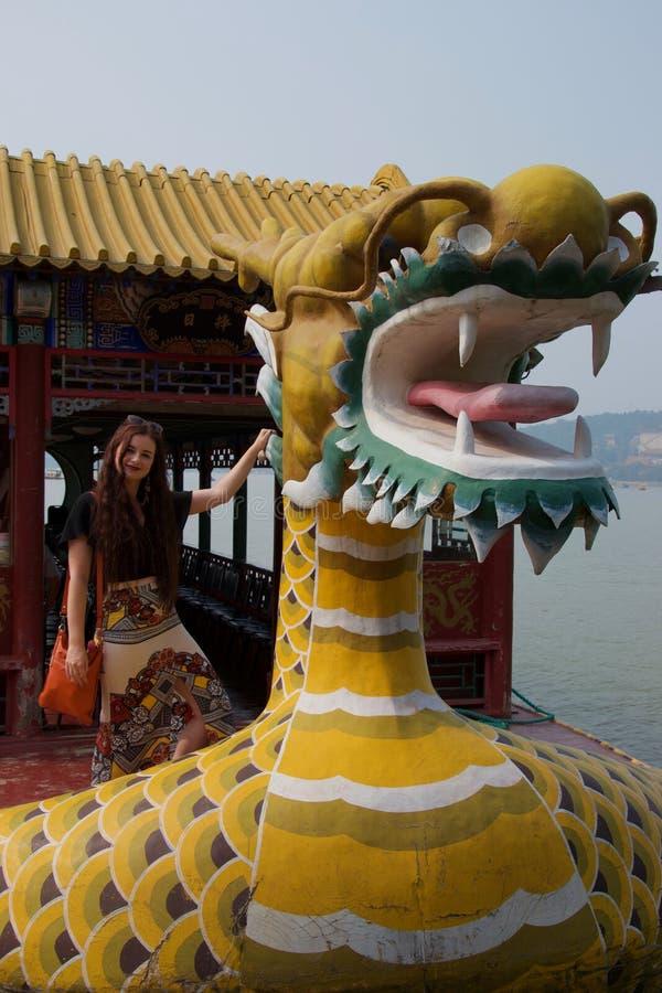 Barco chino del dragón con la presentación femenina occidental del turista foto de archivo