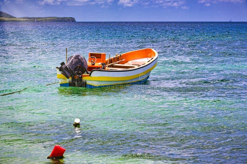 Barco colorido de madeira pequeno no oceano claro da ?gua fotografia de stock