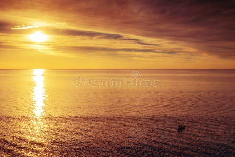 Barco com os pescadores no por do sol fotos de stock