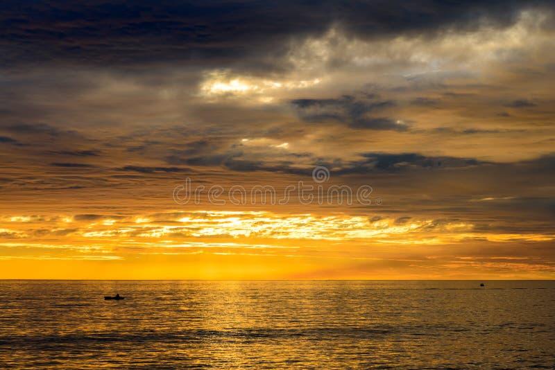 Barco com os pescadores no por do sol imagem de stock