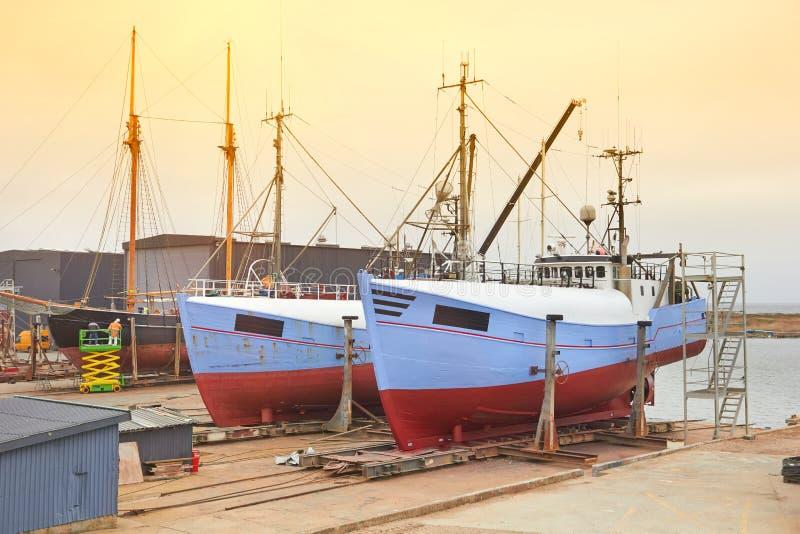 Barco com trabalhadores em um boatyard que está sendo reparado fotos de stock royalty free