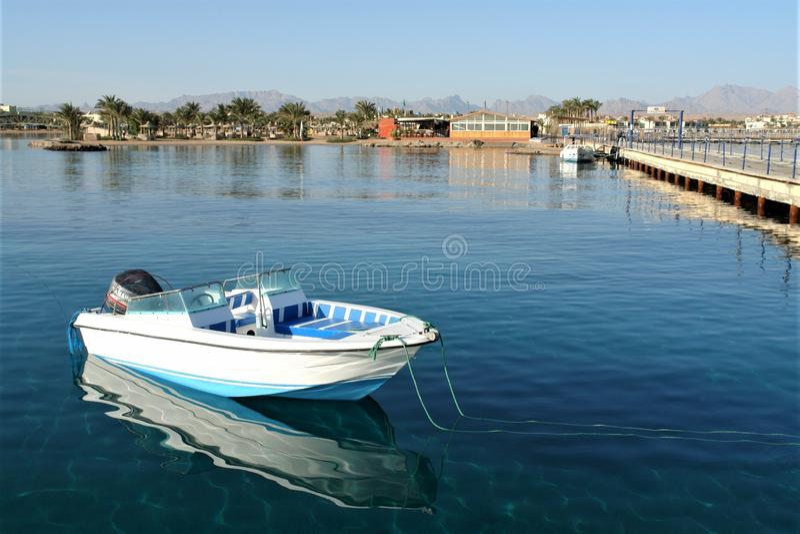 Barco com um motor no cais na água quieta do Mar Vermelho fotos de stock royalty free
