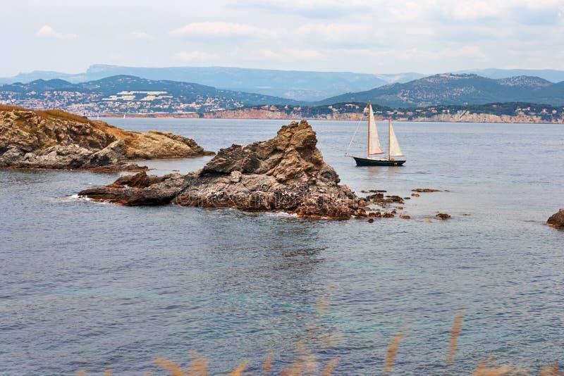 Barco con las velas cerca de la isla foto de archivo libre de regalías