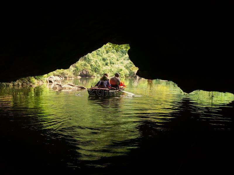 Barco con los turistas que exploran la cueva en un río fotografía de archivo libre de regalías