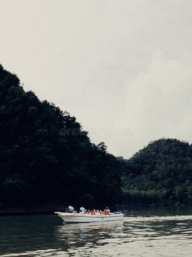 Barco con los turistas que flotan cerca de rocas enormes en parque nacional imagenes de archivo