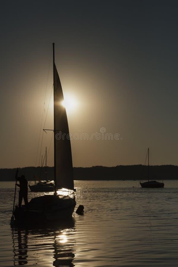 Barco con una vela, salida del sol en el lago imagenes de archivo
