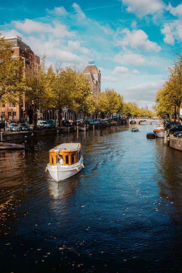 Barco da excursão que cruza em um dos canais famosos de Amsterdão no dia bonito, ensolarado do outono foto de stock