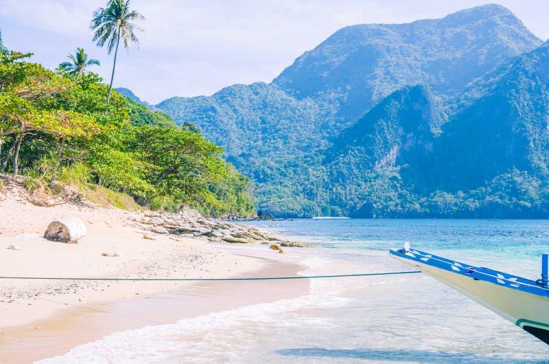 Barco de Banca na âncora na água clara no Sandy Beach perto do EL Nido, Filipinas fotografia de stock royalty free