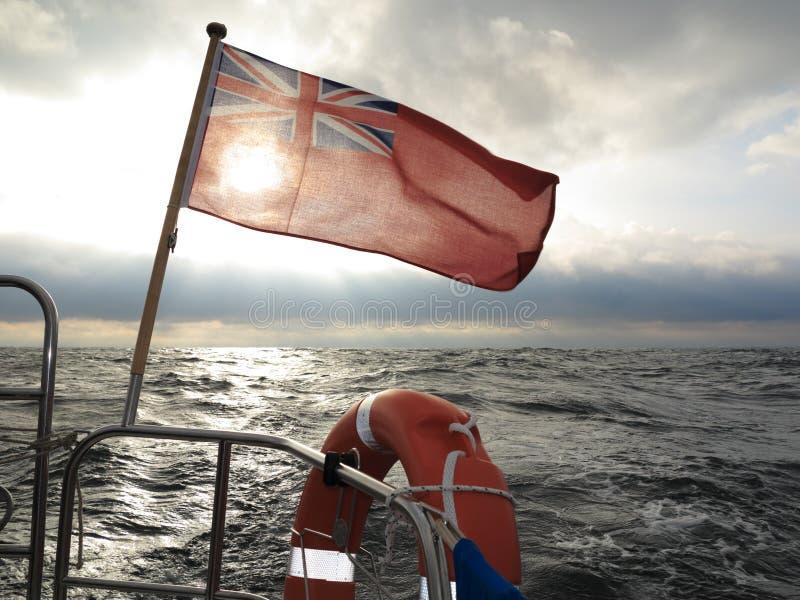 Barco de bandera marítimo británico de la bandera y cielo tempestuoso foto de archivo libre de regalías