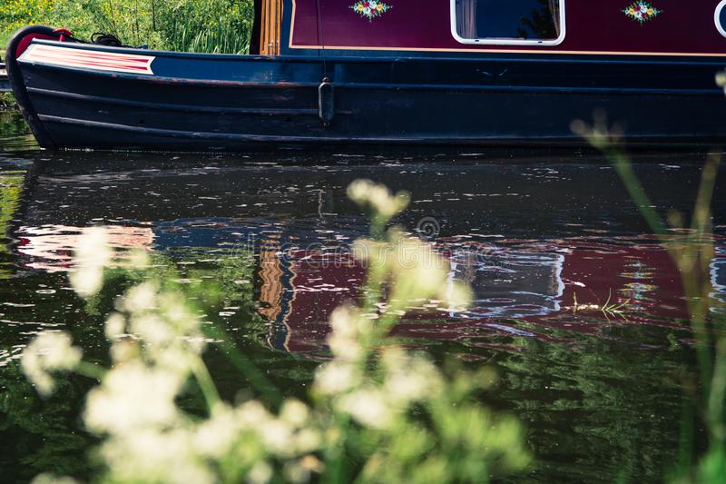 Barco de canal amarrado em um rio em Escócia, Reino Unido com assim fotografia de stock