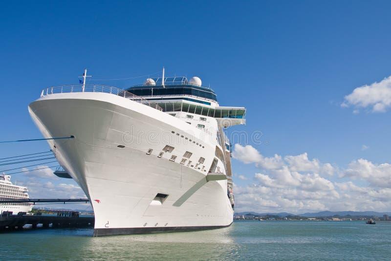 Barco de cruceros blanco enorme atado al embarcadero con la cuerda azul