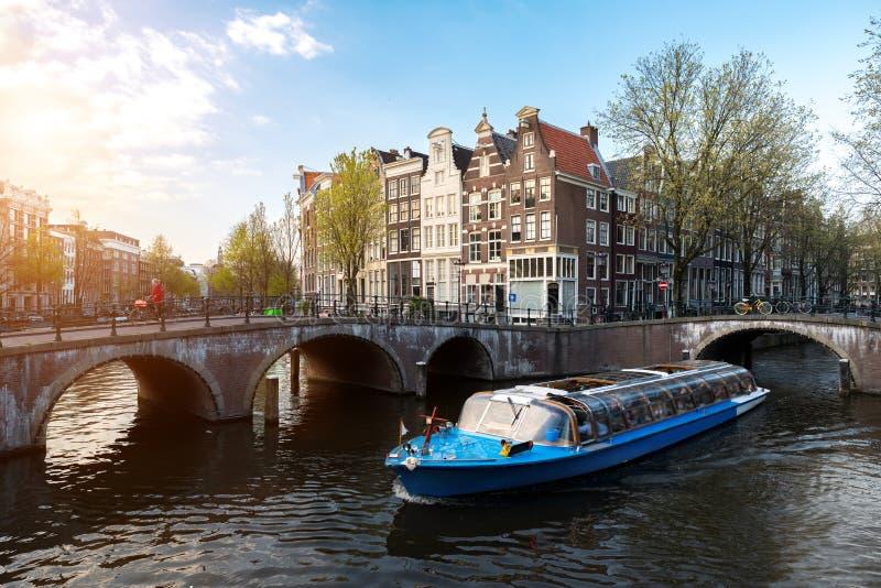 Barco de cruceros del canal de Amsterdam con la casa tradicional holandesa i fotos de archivo