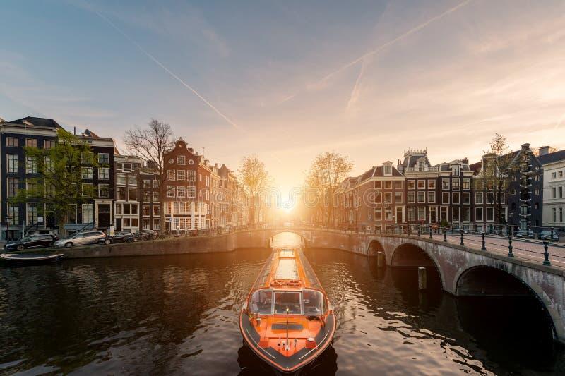 Barco de cruceros del canal de Amsterdam con la casa tradicional holandesa i fotografía de archivo libre de regalías