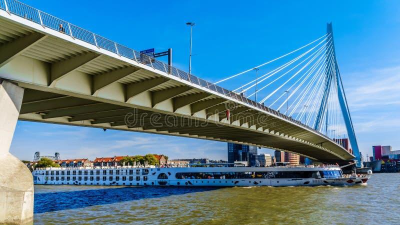 Barco de cruceros del río que va debajo de Erasmus Bridge Cable-permanecido moderno sobre el río de Nieuwe Mosa en Rotterdam imagenes de archivo