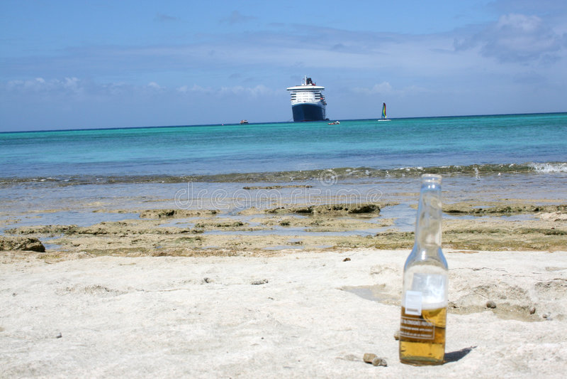Barco de cruceros detrás de la botella de cerveza fotografía de archivo libre de regalías