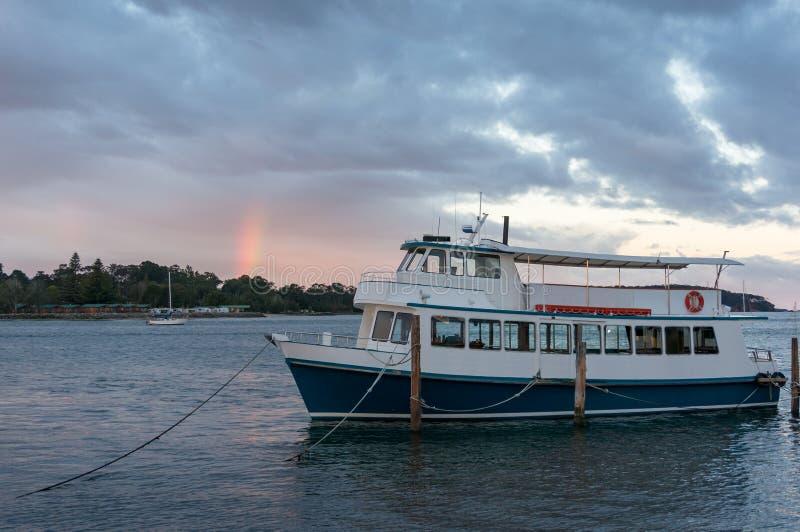 Barco de cruceros, paisaje del transporte del agua con el cielo de la puesta del sol y arco iris imágenes de archivo libres de regalías