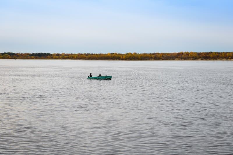 Barco de enfileiramento com os dois homens que navegam ao longo do rio foto de stock royalty free