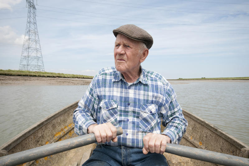 Barco de enfileiramento idoso do homem imagens de stock royalty free