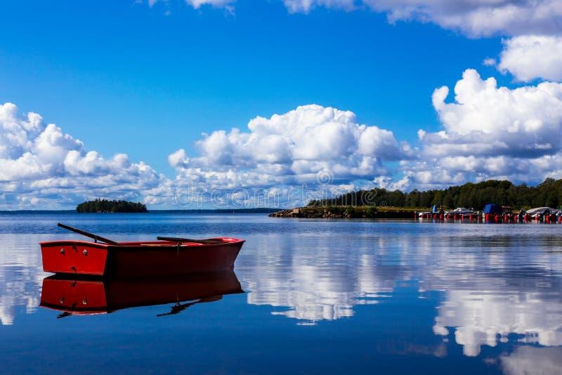 Barco de enfileiramento vermelho em uma baía idílico na Suécia imagem de stock royalty free