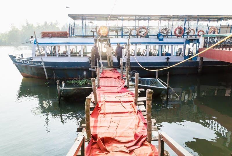 Barco de ferry a lo largo de un muelle con alfombra roja y conductores de barcos indios a lo largo de la vía navegable kollam kot foto de archivo libre de regalías