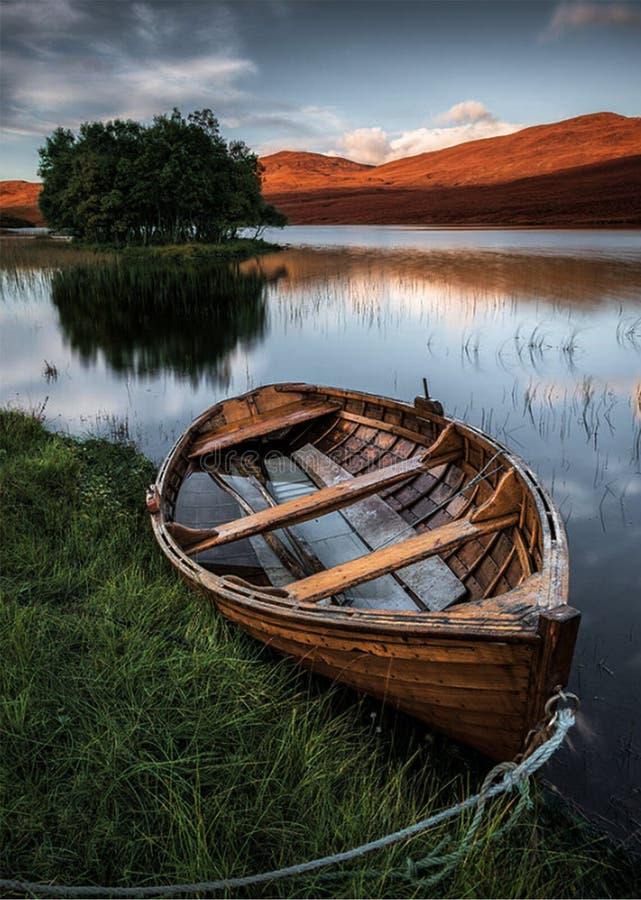 Barco de fila de madera en el lago imagenes de archivo