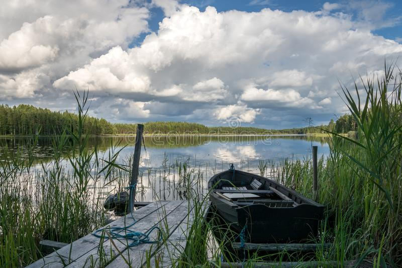 Barco de fileira amarrado a um cais em um lago vítreo na Suécia fotografia de stock royalty free
