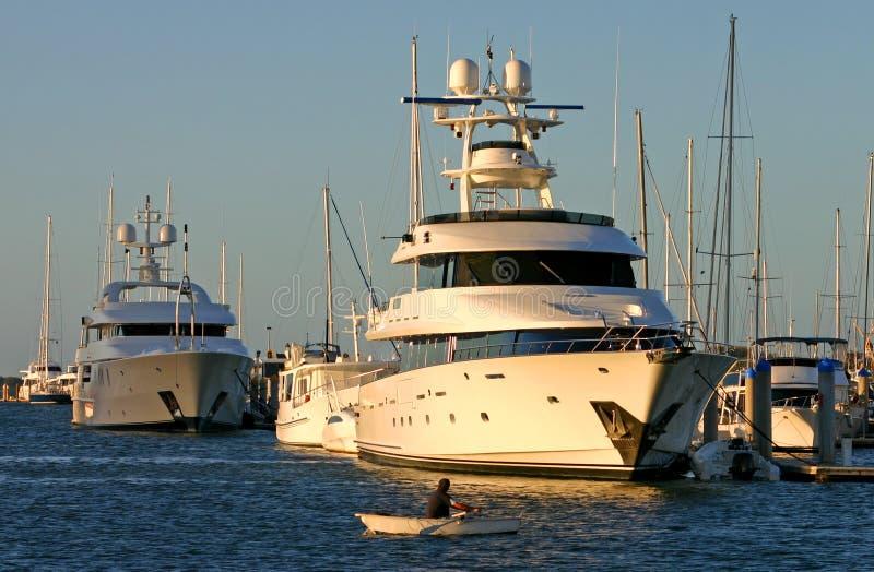 Barco de fileira CONTRA Superyacht fotos de stock royalty free