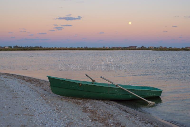 Barco de fileira pequeno no por do sol da costa de mar imagem de stock royalty free