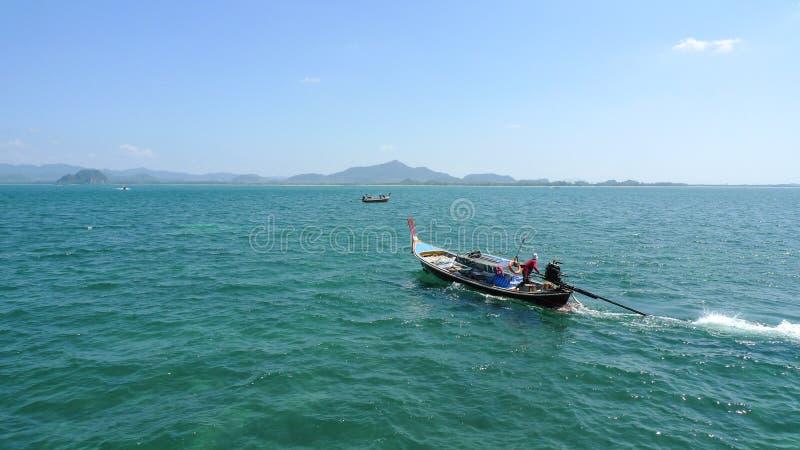 Barco de la cola larga con el marinero en el mar abierto en Tailandia cerca de Koh Muk Island fotografía de archivo