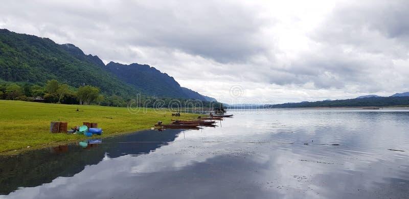 Barco de la cola larga parqueado o que flota en el agua con la hierba verde, el árbol, la montaña grande y el fondo del cielo de  imagenes de archivo