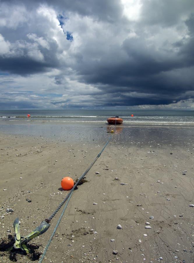Barco de la playa con las nubes de tormenta fotos de archivo