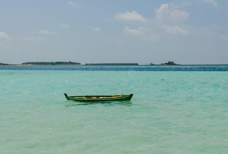 Barco de madeira colorido no Oceano Índico, Maldivas, em casas de campo horizonte-tropicais da ilha e da água contra o céu azul imagens de stock
