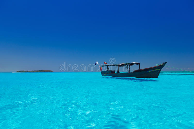 Barco de madeira na água azul torrada fotografia de stock royalty free