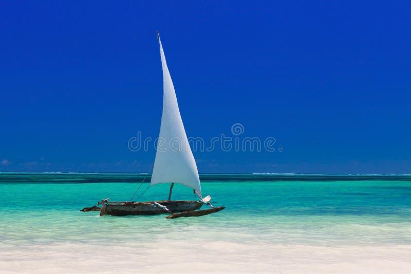Barco de madeira na água azul torrada imagem de stock royalty free