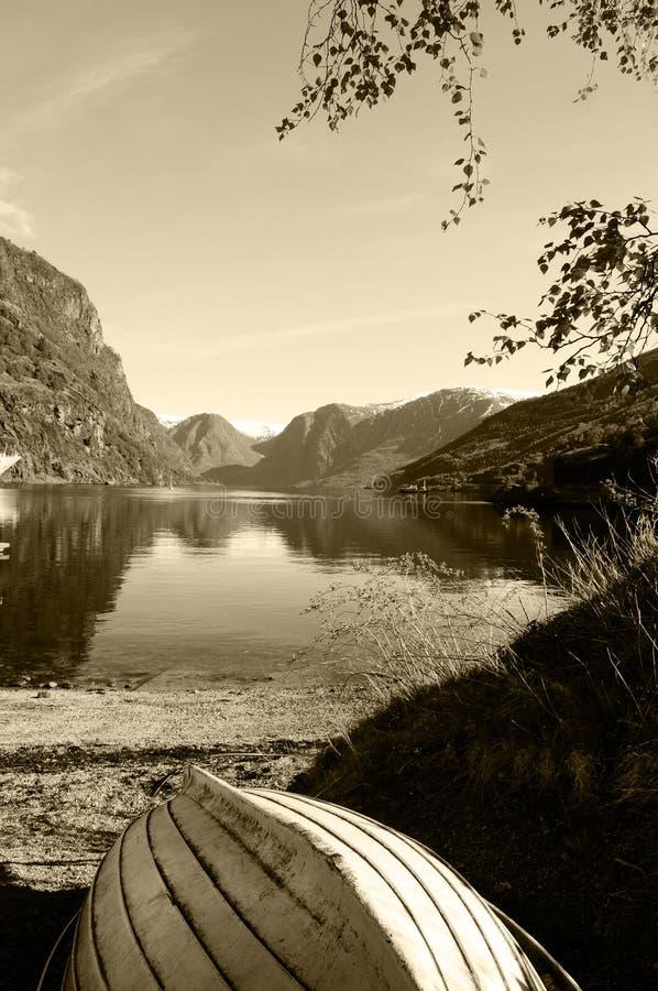 Barco de madeira no lago mountains - paisagem do Sepia fotografia de stock