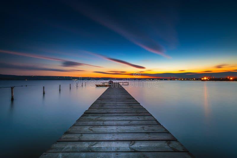 Barco de madeira no lago, tiro da doca e de pesca do por do sol foto de stock