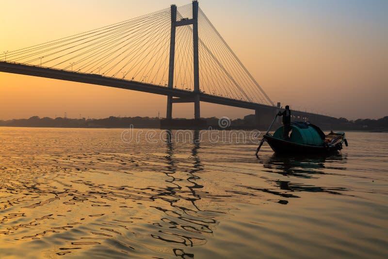 Barco de madeira no rio Hooghly no crepúsculo perto do setu da ponte de Vidyasagar, Kolkata, Índia fotografia de stock royalty free