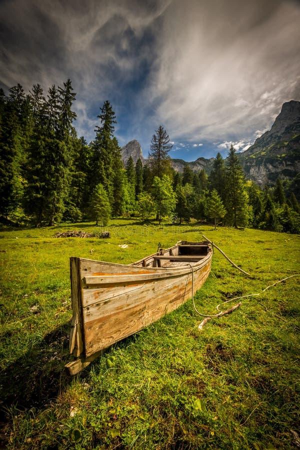 Barco de madeira pequeno pelo lago Gosausee sob Dachstain no prado verde dos cumes perto de Kreidenbach imagem de stock