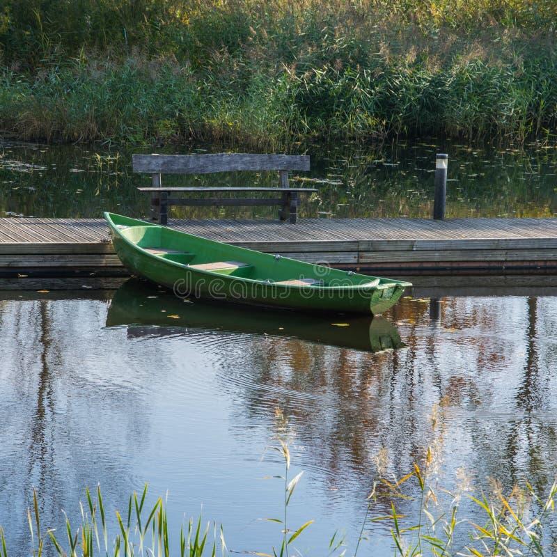 Barco de madeira simples no cais de madeira na lagoa foto de stock