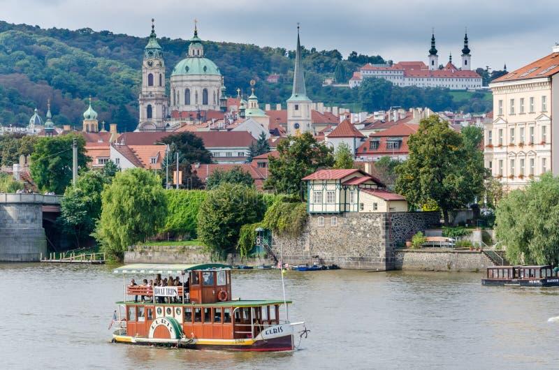 Barco de madera del viaje en el río de Praga con la ciudad y la iglesia históricas en fondo fotografía de archivo libre de regalías