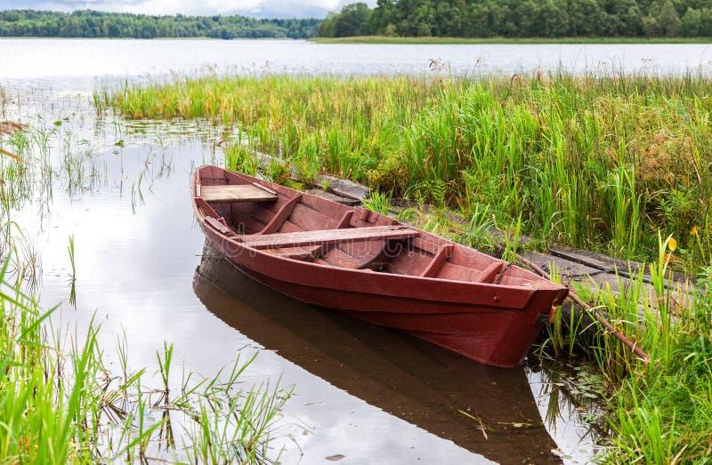 Barco de madera de la vieja pesca en el lago en verano soleado fotografía de archivo