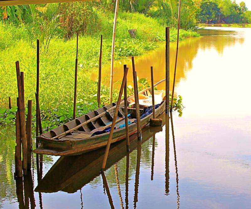 Barco de madera rodeado por el bambú mientras que está parqueado en el canal con los árboles vecinos imagen de archivo