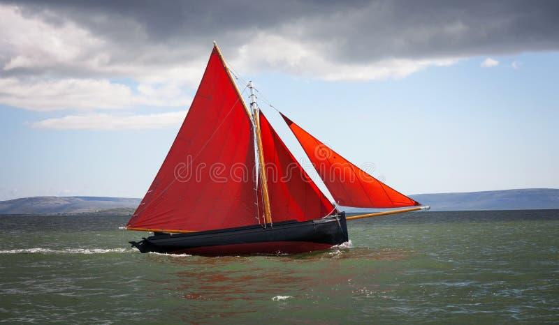 Barco de madera tradicional con la vela roja fotografía de archivo