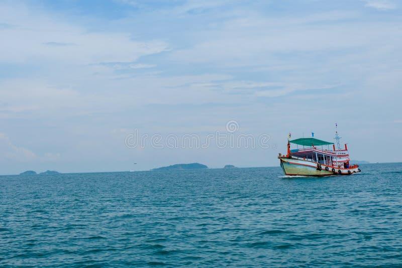 Barco de madera viejo y mar azul debajo del cielo nublado imagen de archivo libre de regalías