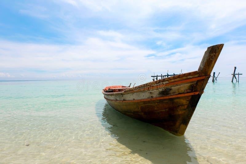 Barco de madera viejo y mar azul debajo del cielo nublado en día soleado foto de archivo